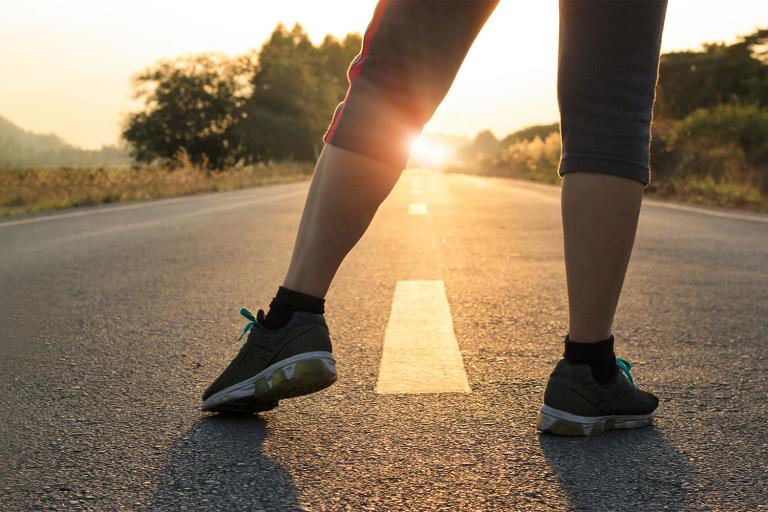 a woman stretching getting ready to run down a long flat stretch of road